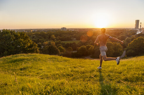 Barechested man running on meadow in park at sunset - DIGF001125
