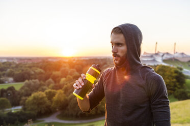 Athlete holding bottle at sunset - DIGF001128