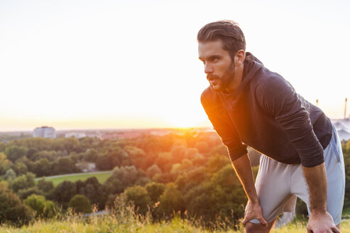 Athlete on a hill having a break at sunset - DIGF001131