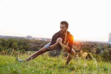 Athlete stretching on meadow at sunset - DIGF001134