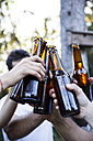 Friends toasting with bottles of beer - ABZF001133