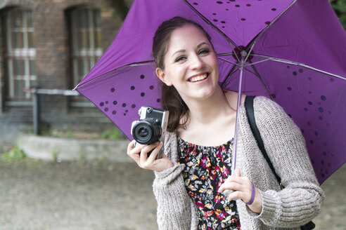 Happy young woman holding camera and umbrella outddors - TAMF000609