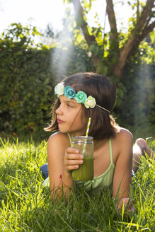 Girl wearing flowers lying on a meadow with smoothie - LVF005256