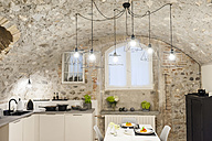 Modern kitchen in old stone house with freshly cooked pasta on table - DIGF001210
