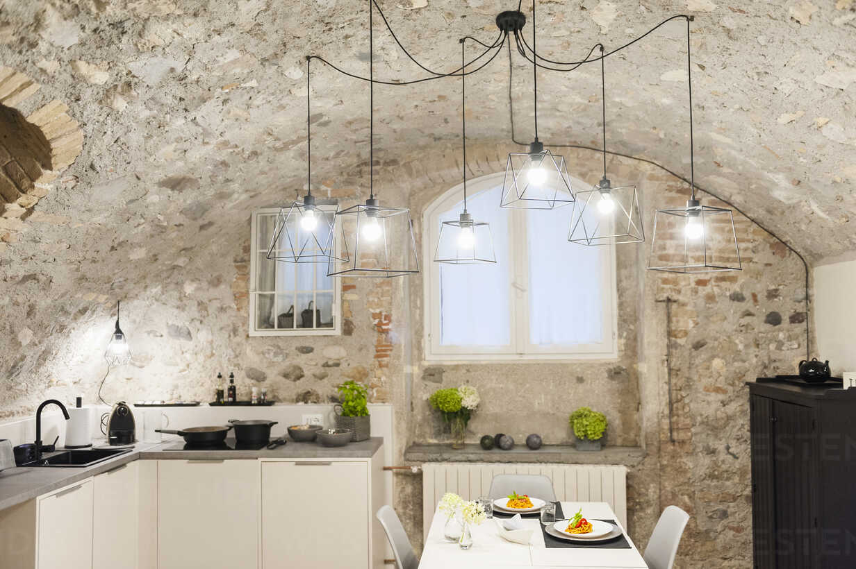 Modern Kitchen In Old Stone House With Freshly Cooked Pasta On Table Stockphoto
