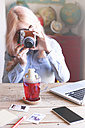 Woman taking an instant photo of a tea glass - RTBF000302