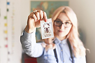 Young woman holding a polaroid of French bulldog - RTBF000314