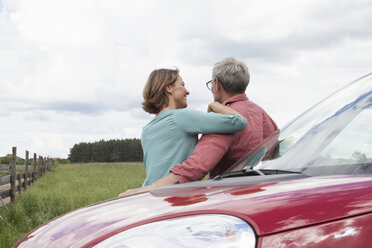 Smiling mature couple resting at car in the countryside - RBF005154