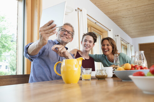 Happy family taking a selfie with tablet at dining table - RBF005160