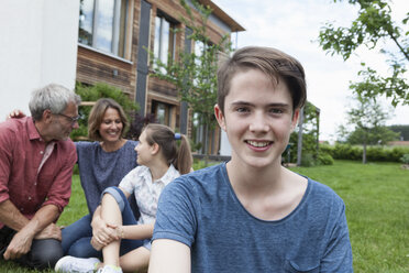 Portrait of smiling teenage boy with his family in garden - RBF005193