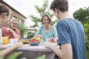 Happy family in garden having afternoon break - RBF005199