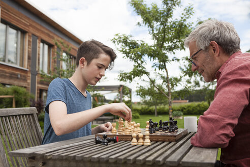 Father and son playing chess in garden - RBF005202