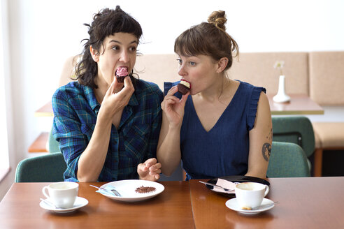 Two friends sitting side by side in a coffee shop eating cup cakes - TSFF000091
