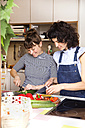 Two friends preparing food together in the kitchen - TSFF000103