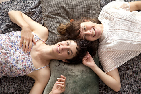 Two smiling friends lying on blanket on the floor at home - TSFF000109
