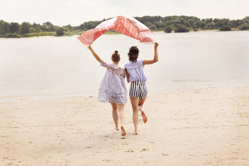 Back view of two friends running side by side on the beach holding cloth over their heads - TSFF000115