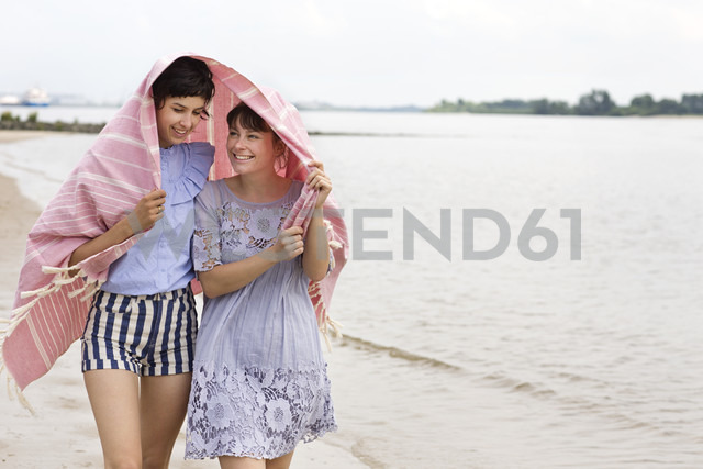 Two happy friends covering themselves with cloth walking side by side on the beach - TSFF000118