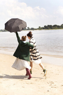 Back view of two friends running side by side on the beach with an umbrella - TSFF000124