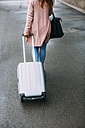 Back view of walking woman with wheeled luggage - EBSF001716
