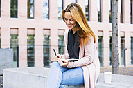 Smiling young woman sitting on bench with notebook and coffee to go - EBSF001719