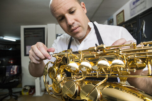 Instrument maker dismounting a saxophone during a repair - ABZF001157