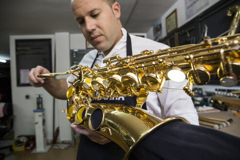Instrument maker dismounting a saxophone during a repair - ABZF001160