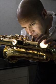 Instrument maker repairing a saxophone - ABZF001163