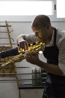 Instrument maker using a scraper during a saxophone repair - ABZF001166
