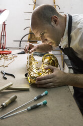Instrument maker dismounting a saxophone during a repair - ABZF001172