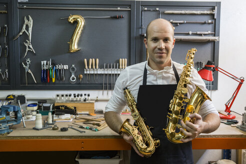 Portrait of an instrument maker holding two saxophones in his workshop - ABZF001181