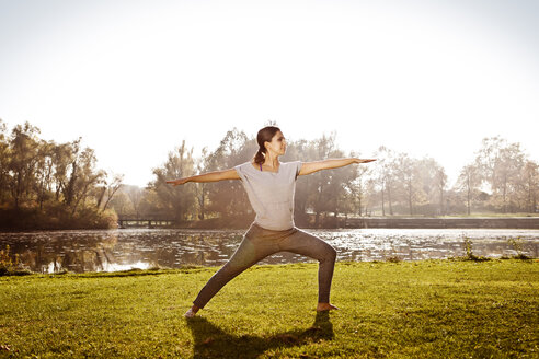 Woman standing in Virabhadrasana position at lakeside - MFF003053