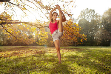 Woman holding a tai chi pose in autumnal park - MFF003062
