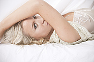 Blond woman in lingerie lying on bed - MFF003077
