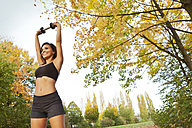 Smiling woman exercising with a weight outdoors - MFF003170