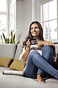 Smiling woman relaxing on couch holding a mug - MFF003173