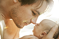 Father getting close to the face of his newborn baby - MFF003194