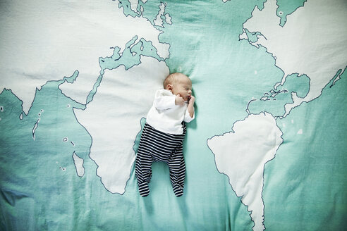 Newborn baby sleeping on blanket with world map - MFF003200