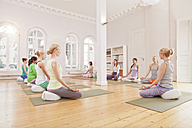 Group of women in yoga studio sitting in Lotus pose with instructor - MFF003206