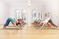Group of people in yoga studio holding down dog pose - MFF003212
