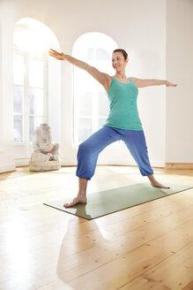 Woman in sunny yoga studio holding Virabhadrasana pose - MFF003227