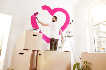 Young man painting a pink heart on a wall in new apartment - MFF003269