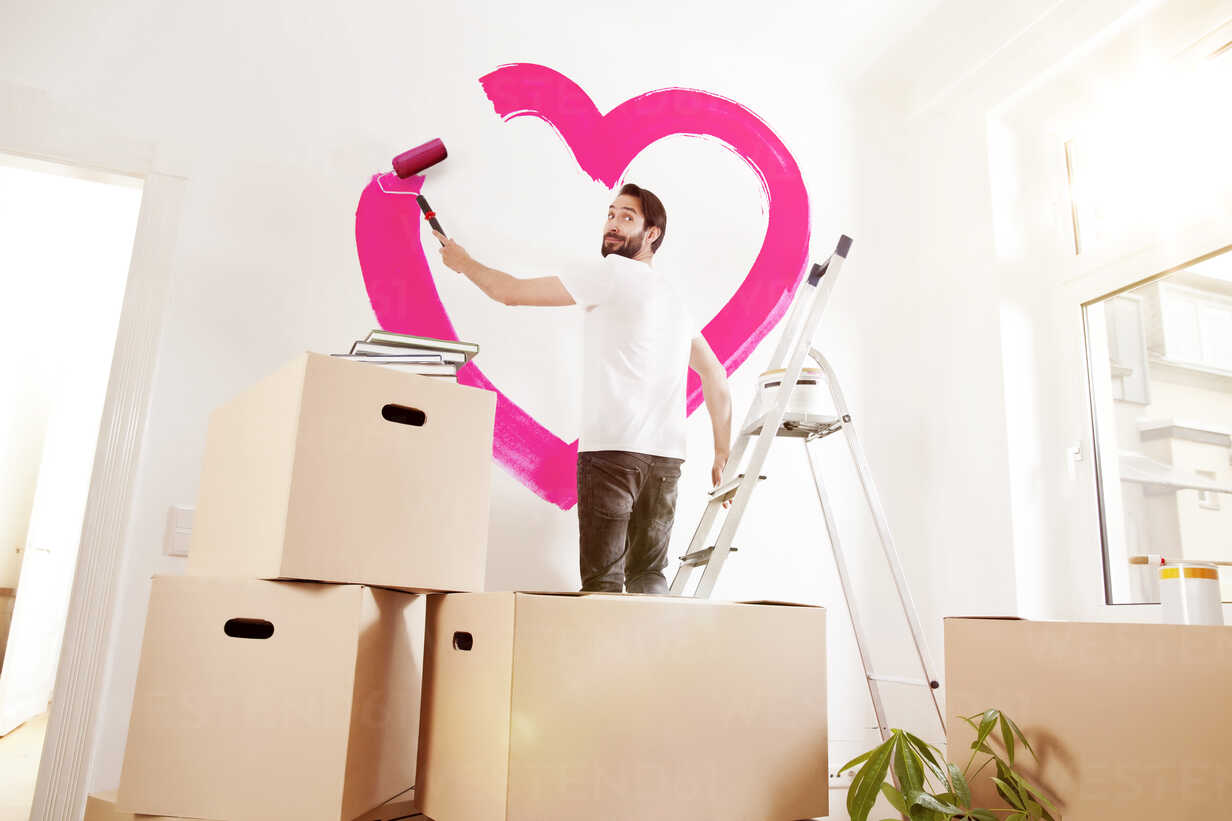 Young man painting a pink heart on a wall in new apartment - MFF003269 - Mareen Fischinger/Westend61