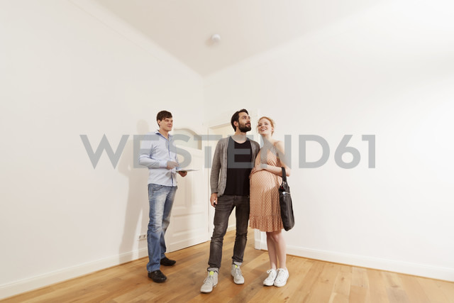 Real estate agent showing expecting parents around in a new apartment - MFF003275