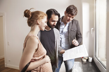 Real estate agent showing expecting parents a contract in a new apartment - MFF003278