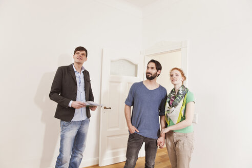 Real estate agent showing a couple around in a new apartment - MFF003281