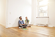 Young couple sitting on floor in empty apartment - MFF003287