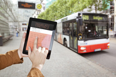 Hand holding a digital tablet with bus time table at a bus station - MFF003299