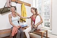 Two young women having fun in yoga studio changing room - MFF003311