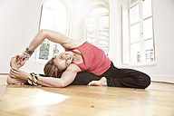 Woman stretching herself in Parivrtta Uphavistha Konasana yoga pose in studio - MFF003326