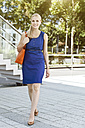Smiling young woman in blue dress on the go - MFF003335